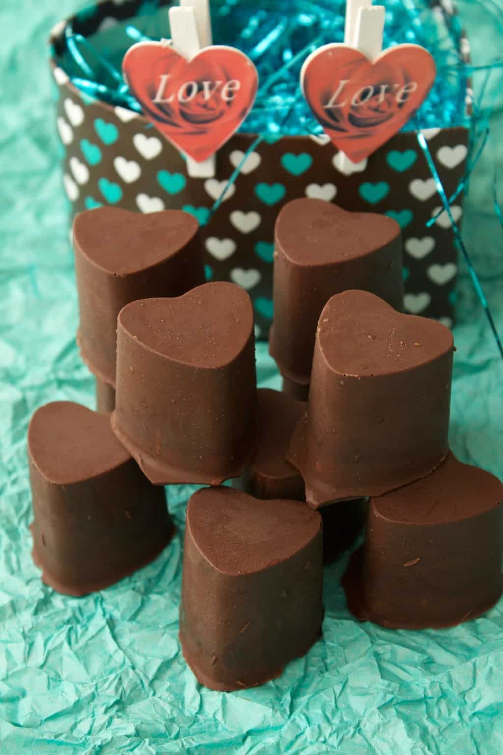 Heart-shaped vegan chocolate caramels on green tissue paper.