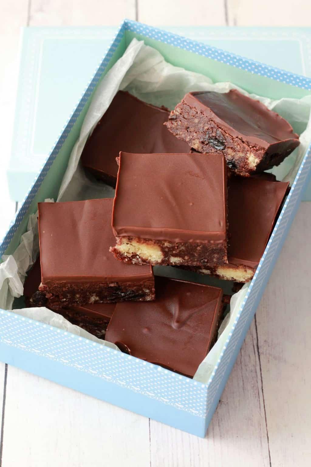 Chocolate Tiffin Squares - crushed shortbread cookies and raisins surrounded in rich chocolate #vegan #lovingitvegan #chocolate #tiffin #dessert #dairyfree