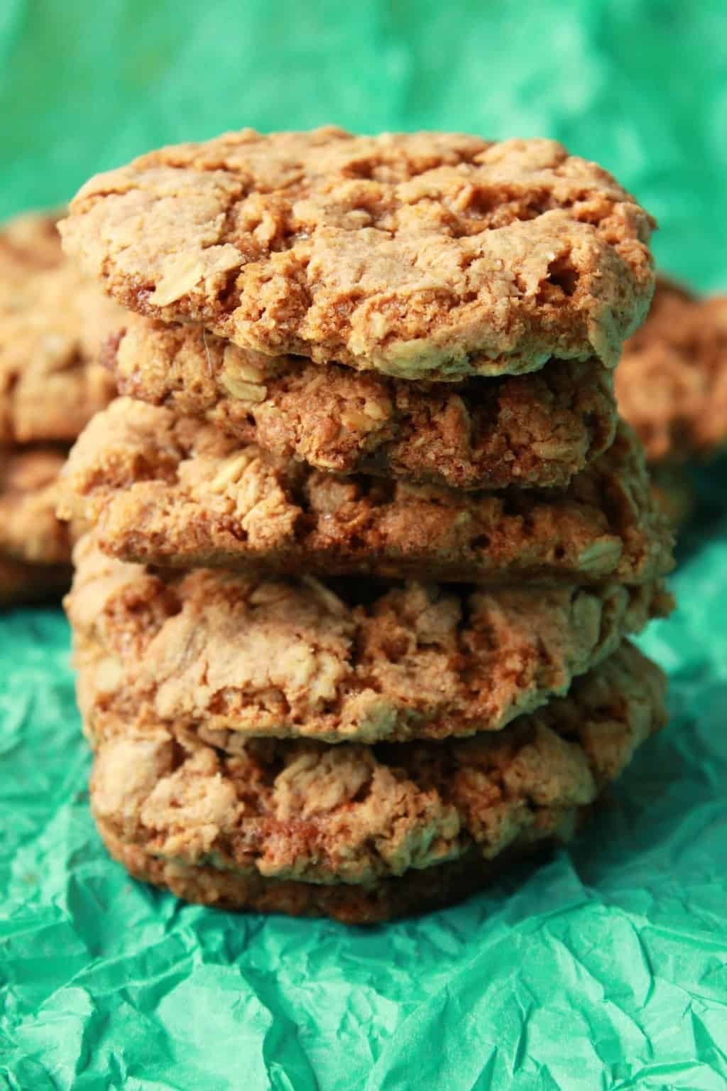 Vegan oatmeal cookies stacked up against a green background.