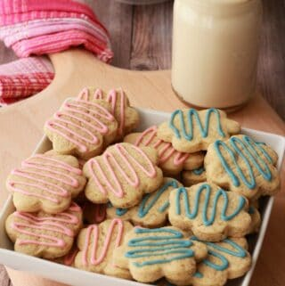 Vegan sugar cookies stacked up in a white bowl.