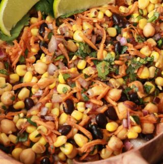 Black bean and corn salad in a wooden salad bowl with a serving spoon.