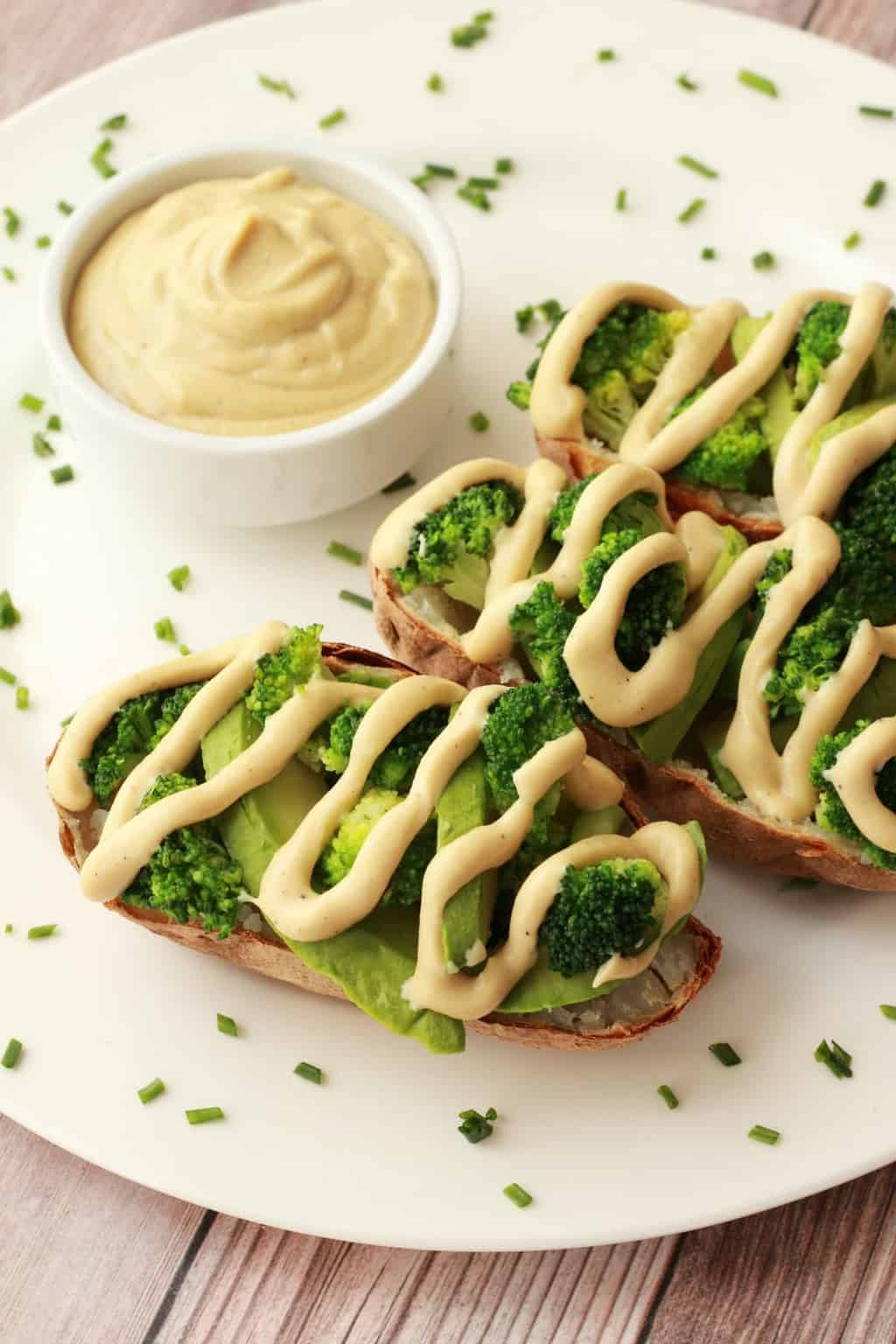 Cashew cheese sauce drizzled over baked potatoes and broccoli on a white plate.