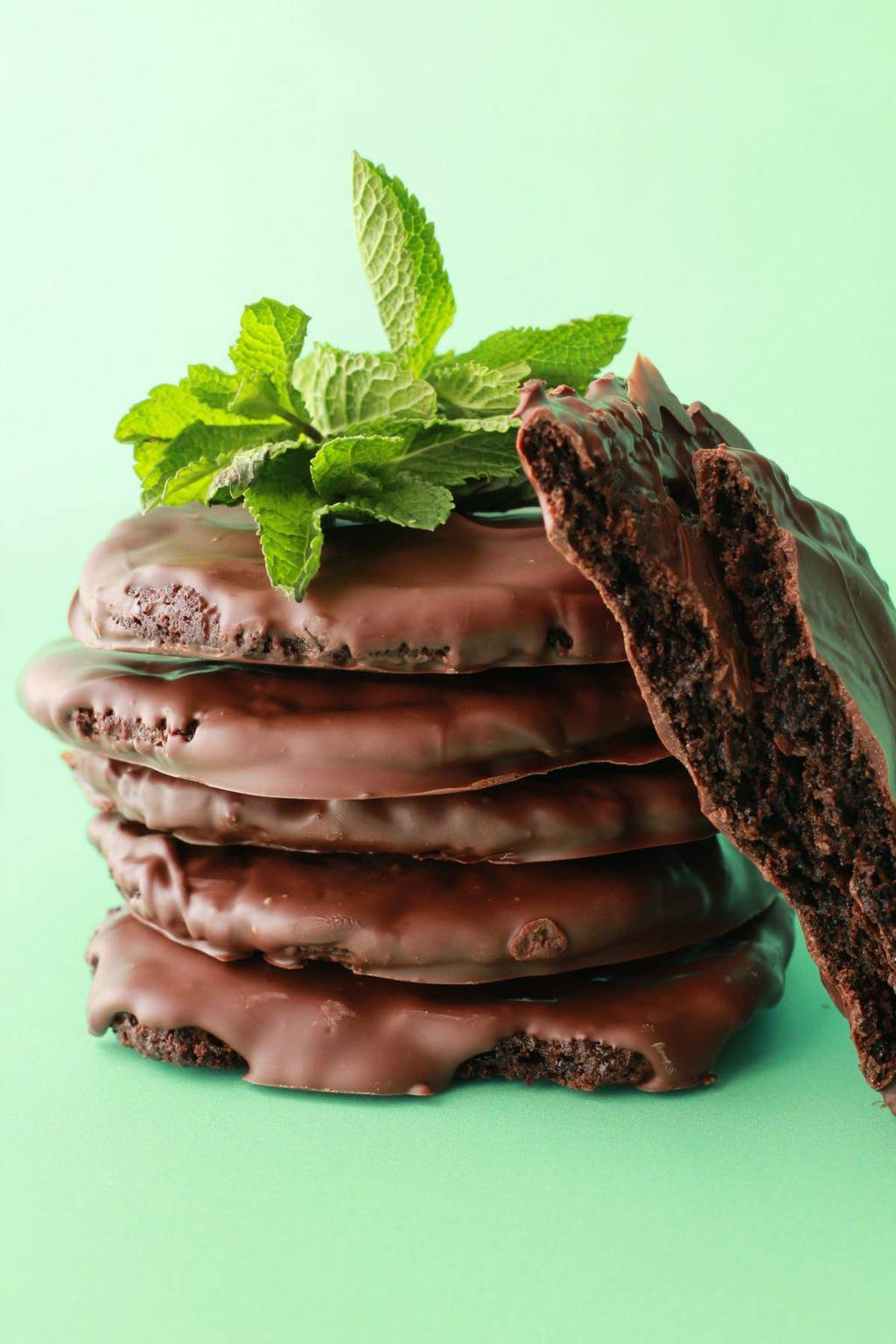 Vegan thin mint cookies stacked up with fresh mint leaves against a green background.