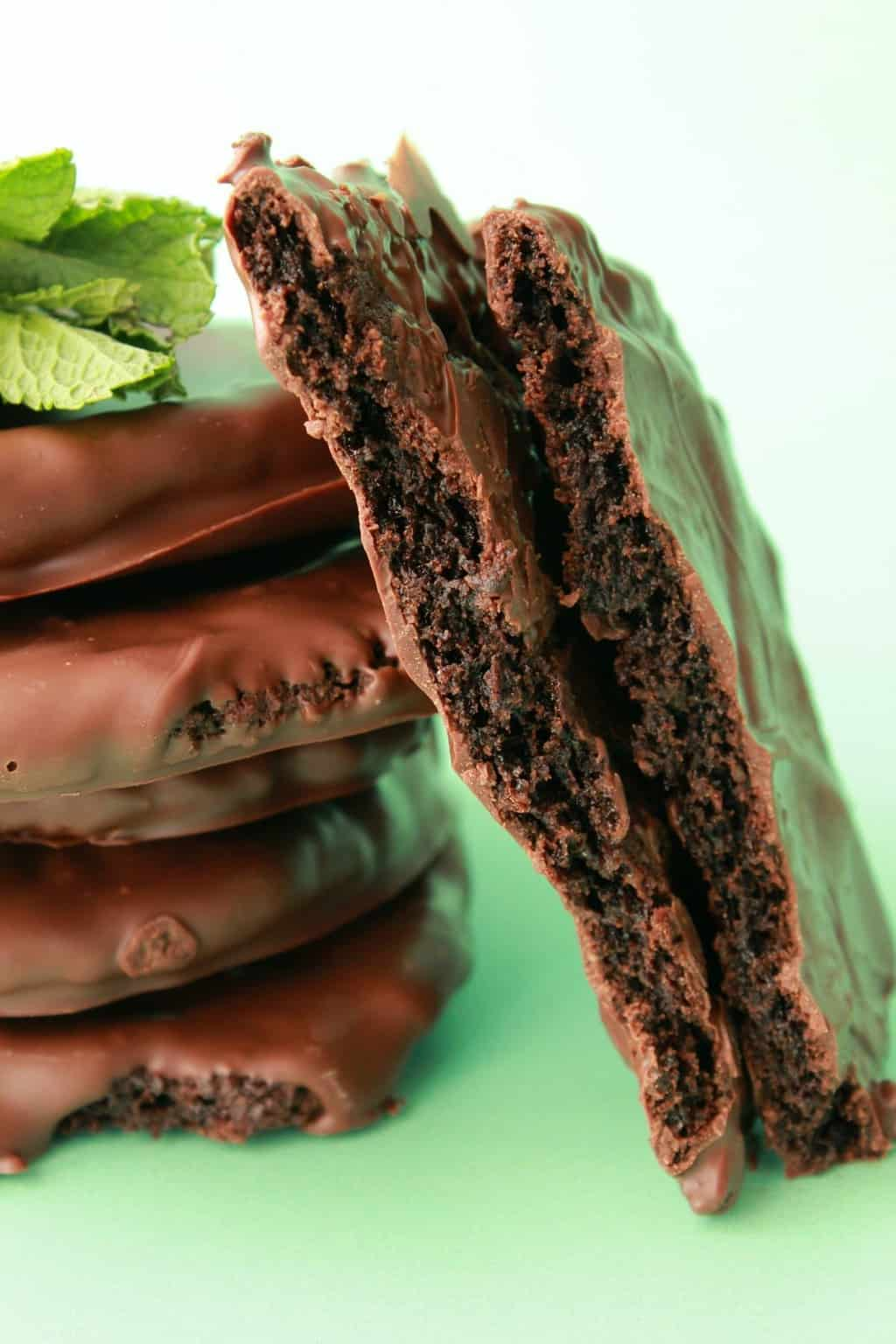 Vegan thin mint cookies stacked up with fresh mint. One cookie broken in half to show the centers.