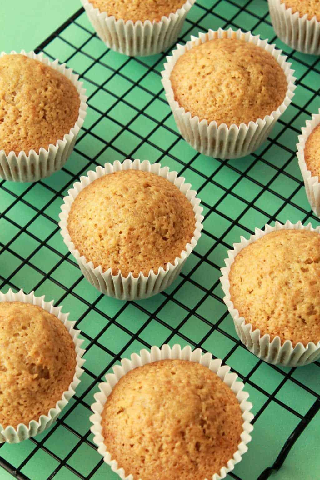 Vegan lemon cupcakes freshly baked on a wire cooling rack.