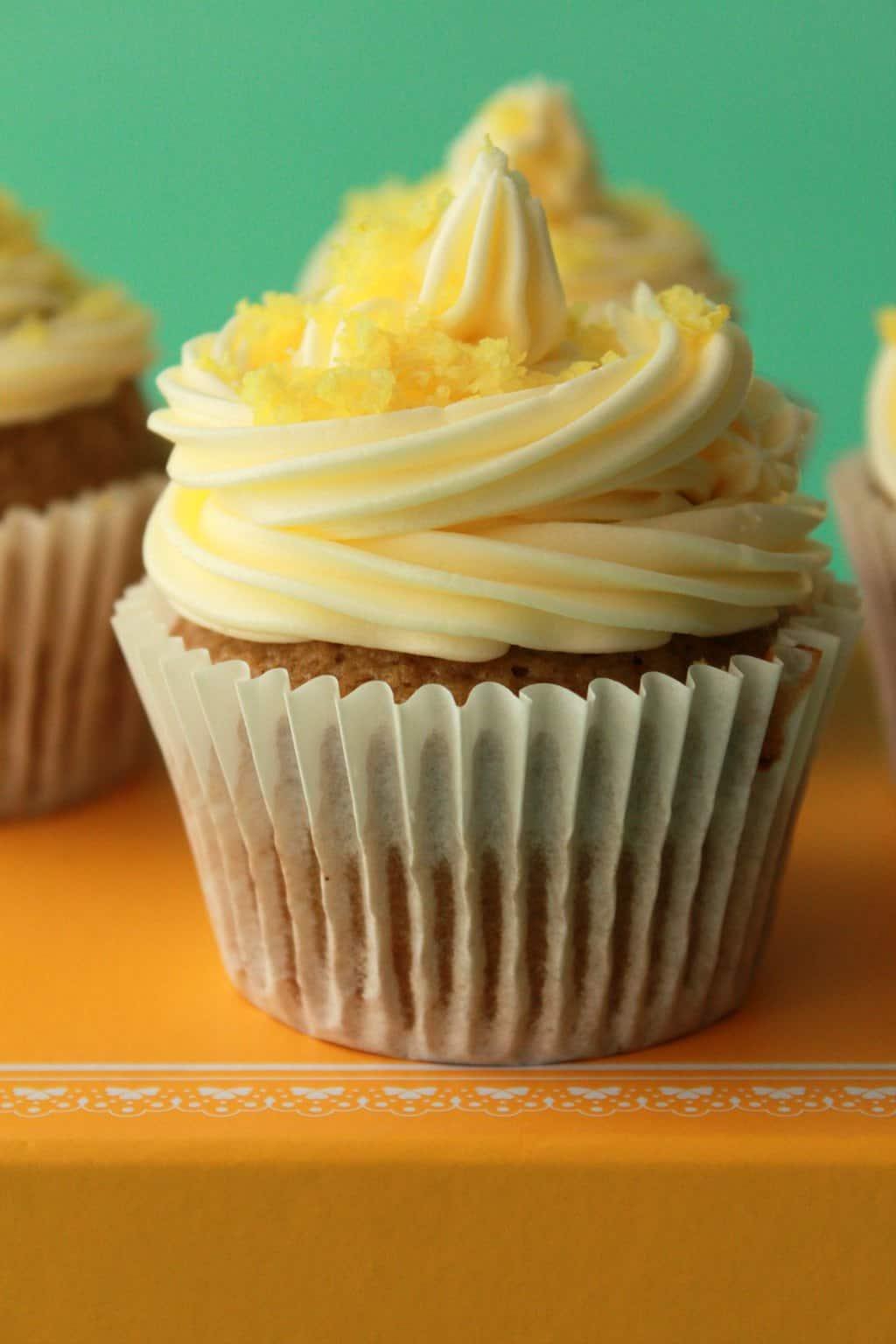 Vegan lemon cupcakes topped with lemon frosting and lemon zest.