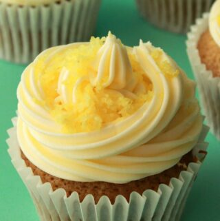 Lemon cupcakes topped with frosting and lemon zest.