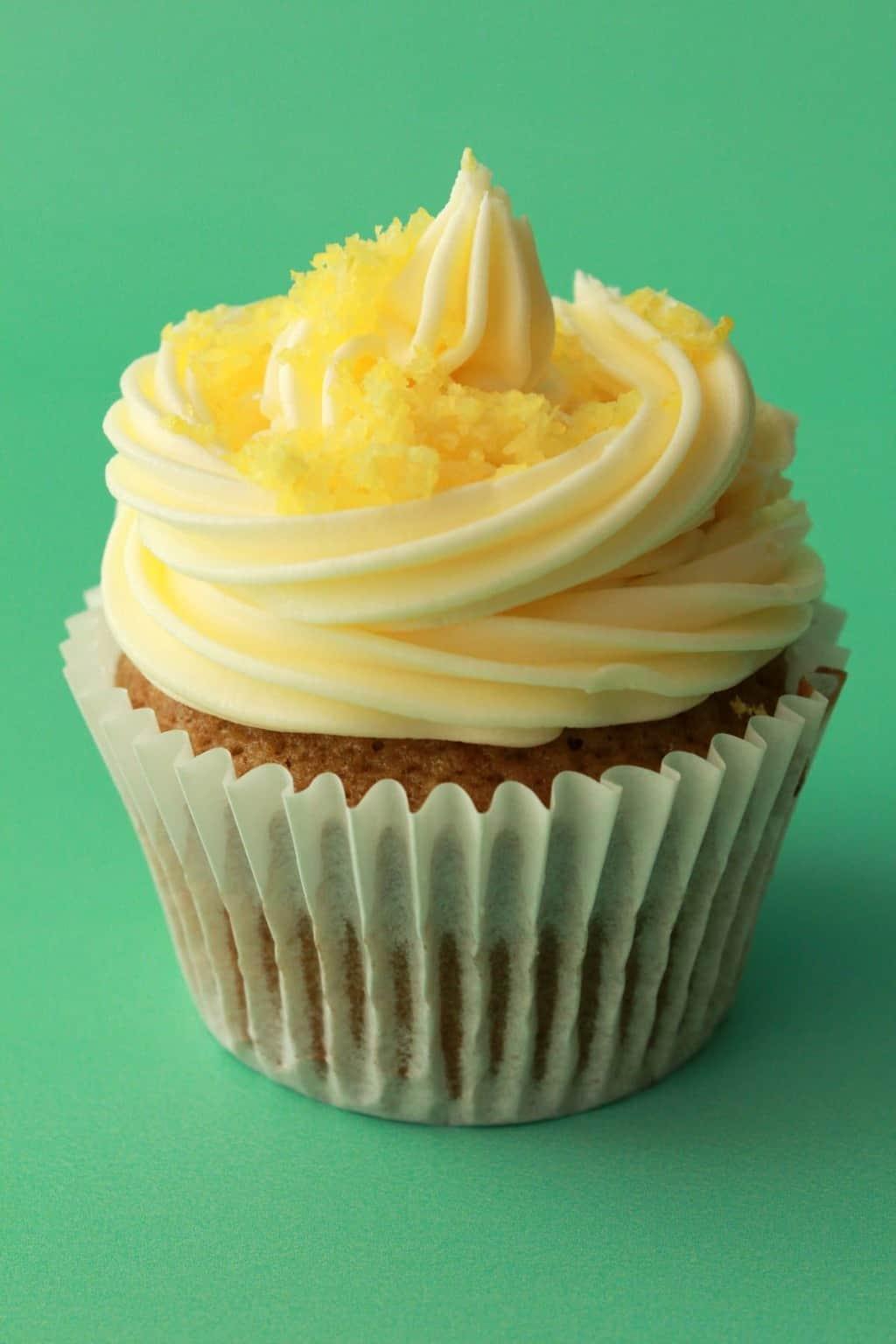 Vegan lemon cupcake topped with lemon frosting and lemon zest.