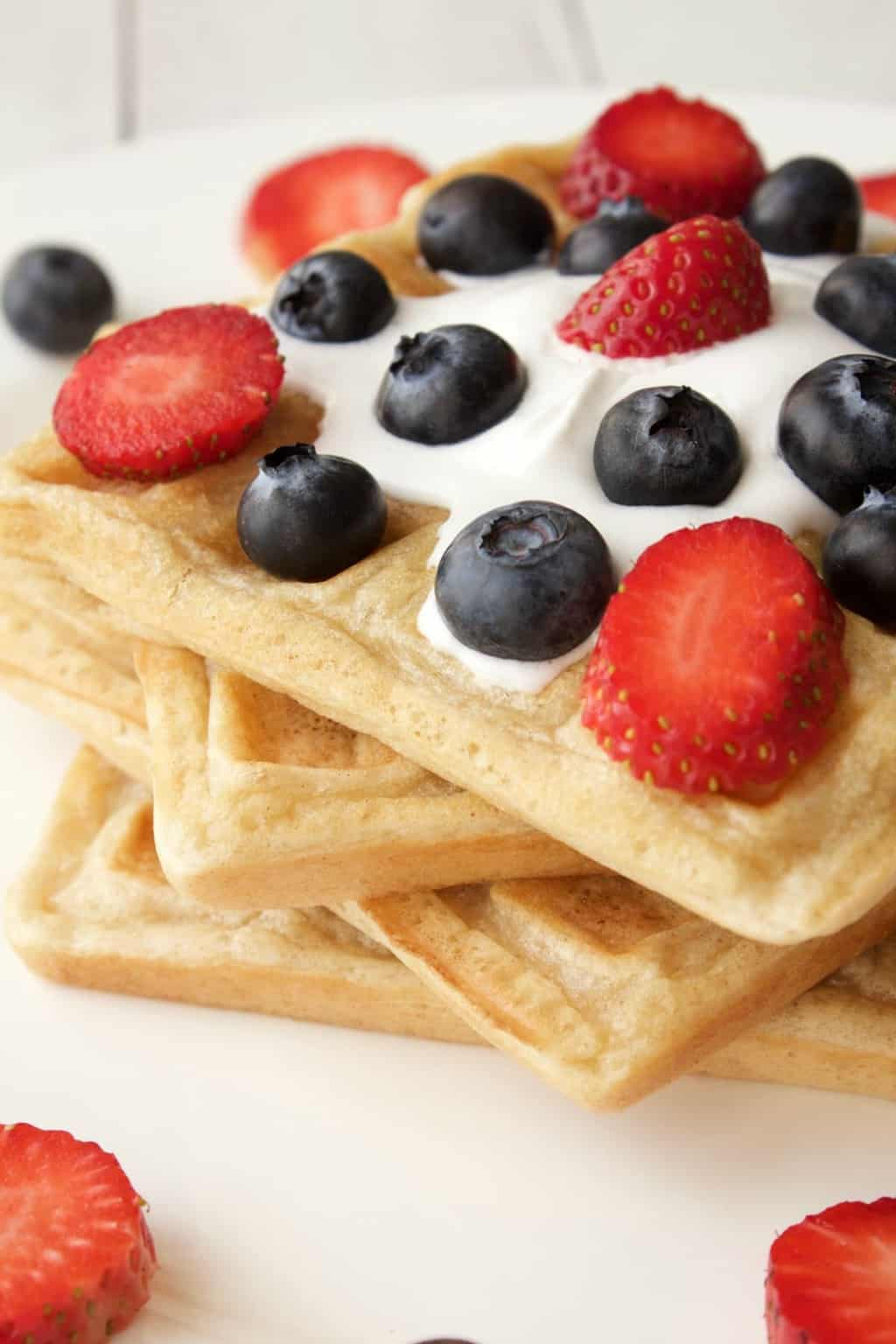 Vegan waffles topped with vegan cream, strawberries and blueberries on a white plate.