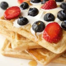 Vegan waffles topped with cream and berries on a white plate.
