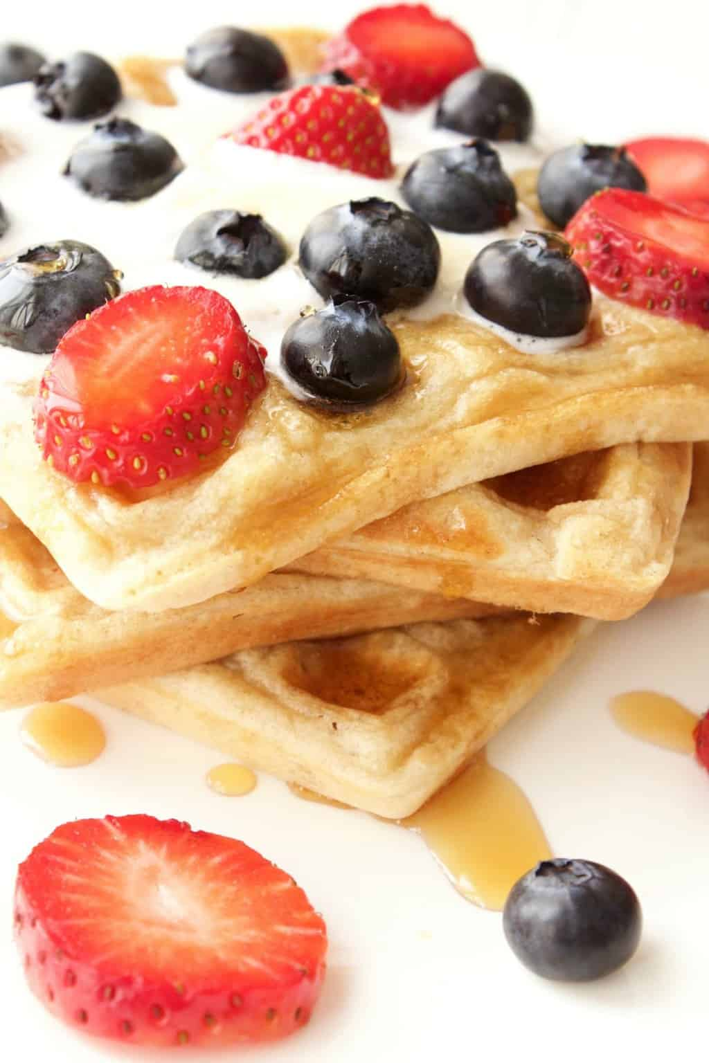 Vegan waffles topped with vegan cream, maple syrup, strawberries and blueberries, on a white plate.