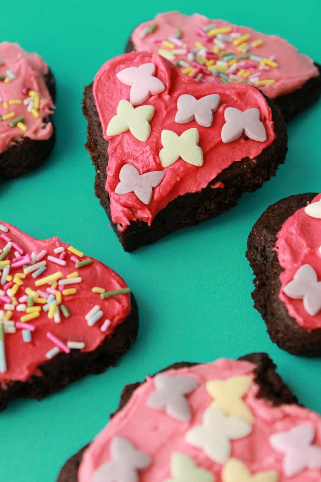 Vegan chocolate sugar cookies with pink frosting and sprinkles.