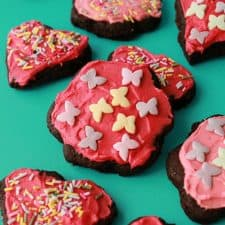 Vegan chocolate sugar cookies topped with frosting and sprinkles.