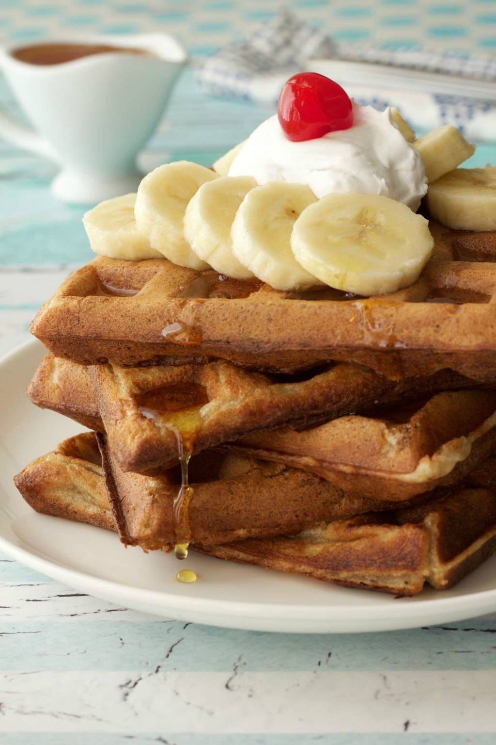 Vegan Banana Waffles. Perfect for breakfast served with whipped coconut cream, sliced bananas and syrup. #vegan #lovingitvegan #bananawaffles #breakfast