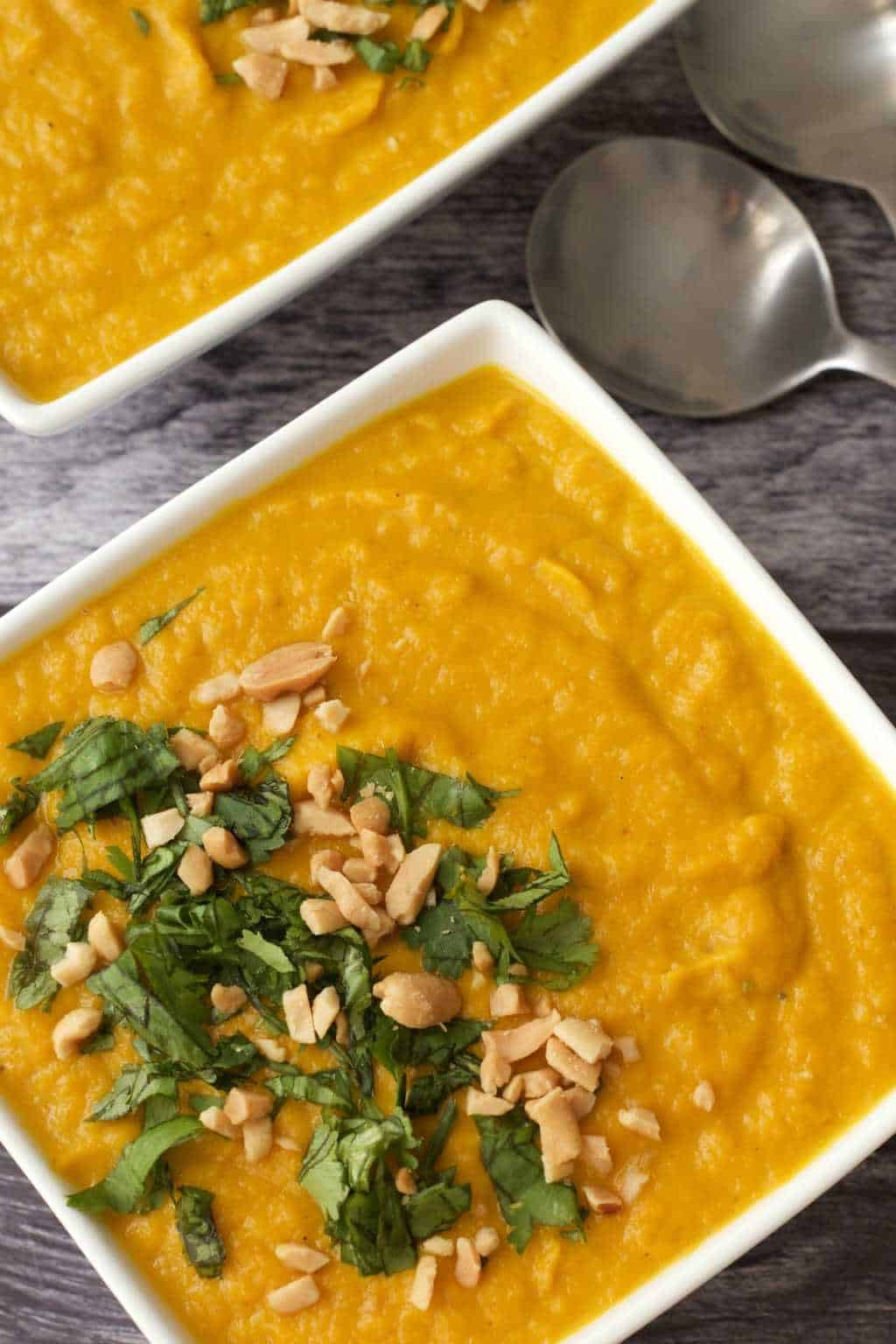 Vegan carrot soup topped with peanuts and chopped cilantro in white bowls.