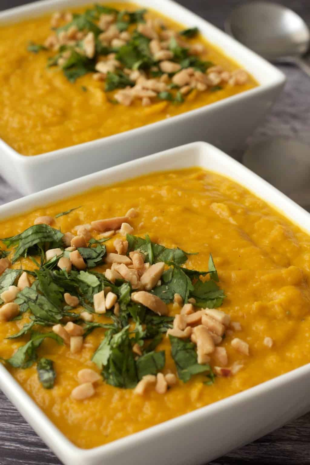 Vegan carrot soup topped with chopped cilantro and peanuts in white bowls.