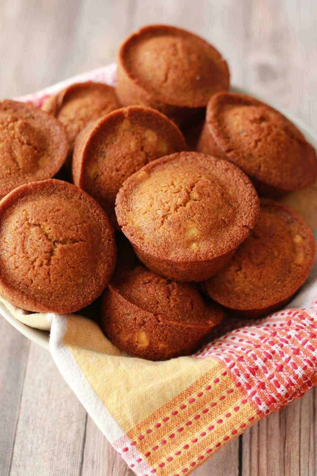 Vegan cornbread muffins stacked up in a bowl.