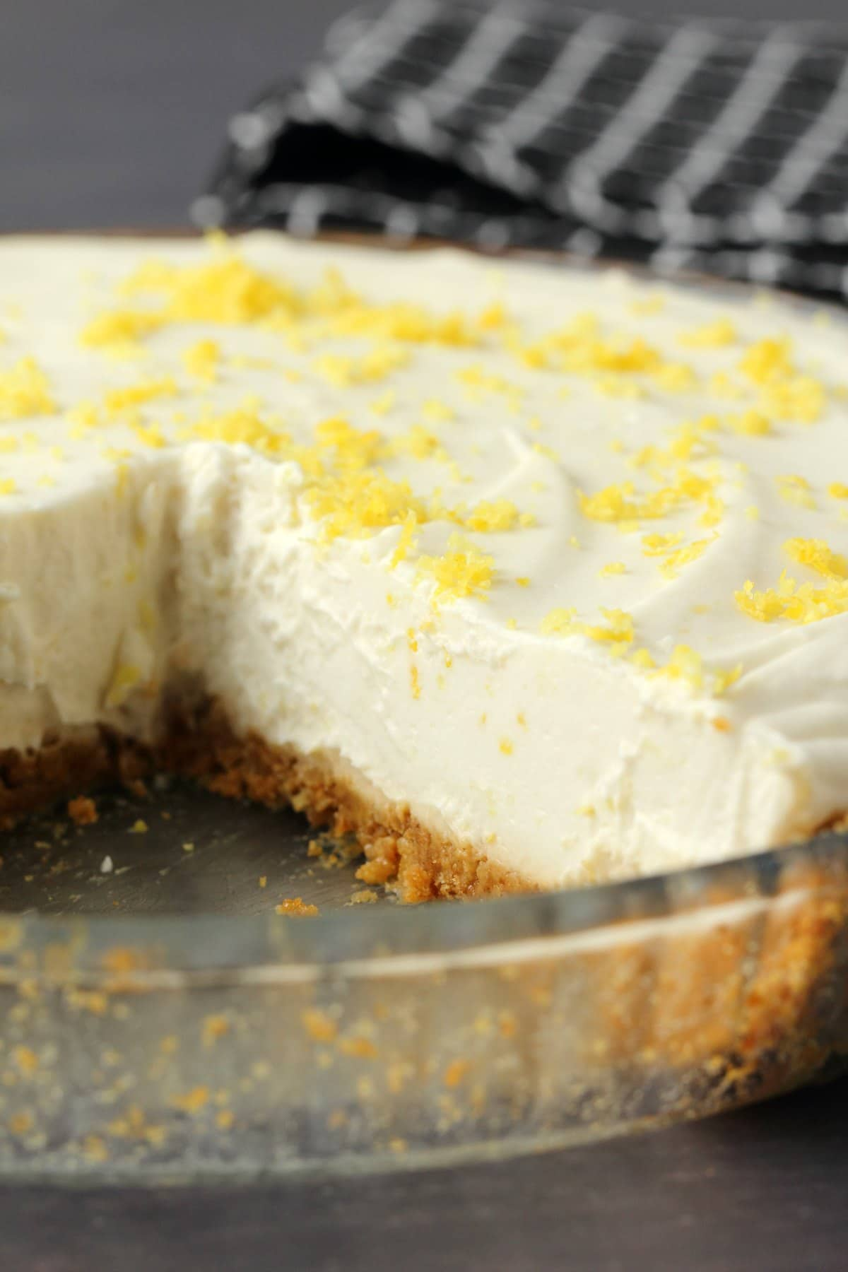 Vegan lemon pie in a glass pie dish, one slice removed.