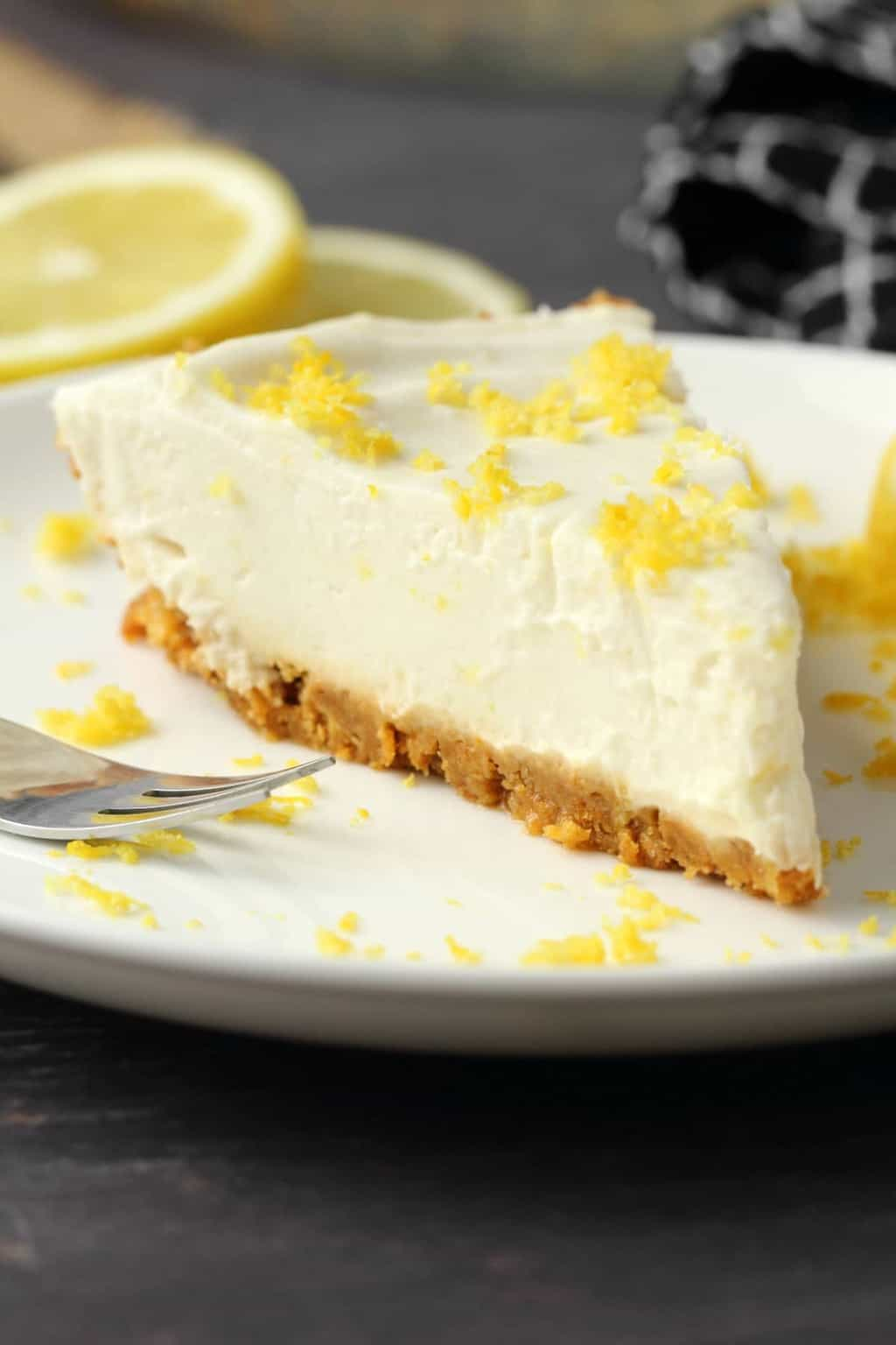 Slice of vegan lemon pie on a white plate with a cake fork.