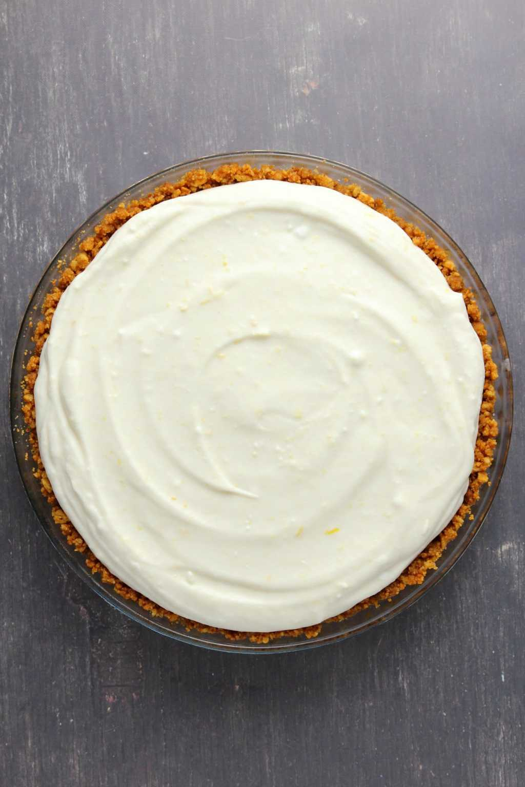 Crushed cookie pie base and lemon filling for a vegan lemon pie.