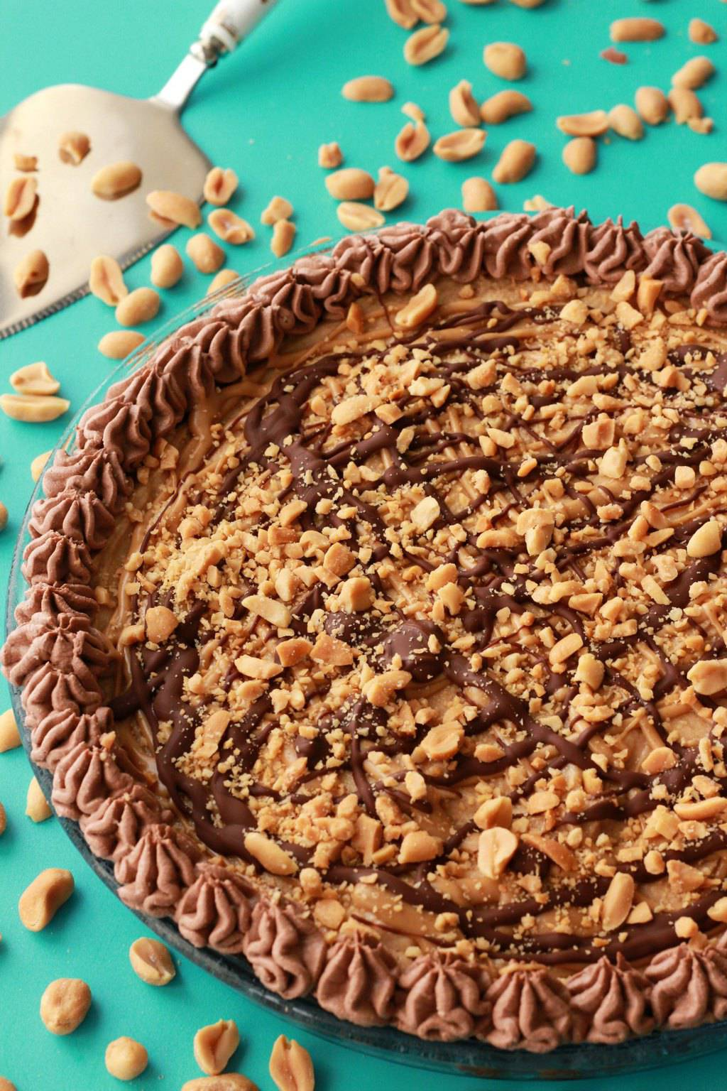Vegan peanut butter pie topped with melted peanut butter and chocolate and crushed peanuts in a glass pie dish.