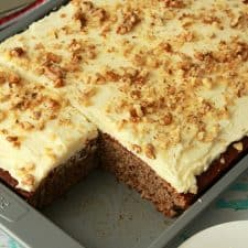 Vegan banana cake topped with frosting and chopped walnuts.