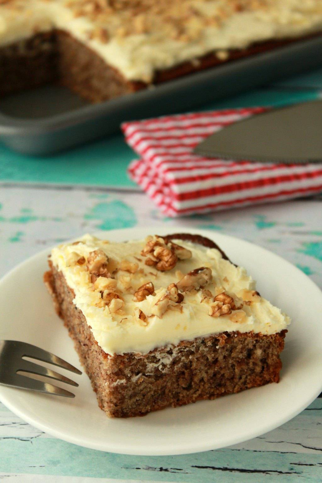 Moist and Delicious Vegan Banana Cake with Lemon Frosting and crushed walnuts. Light and fluffy. #vegan #lovingitvegan #bananacake #dessert