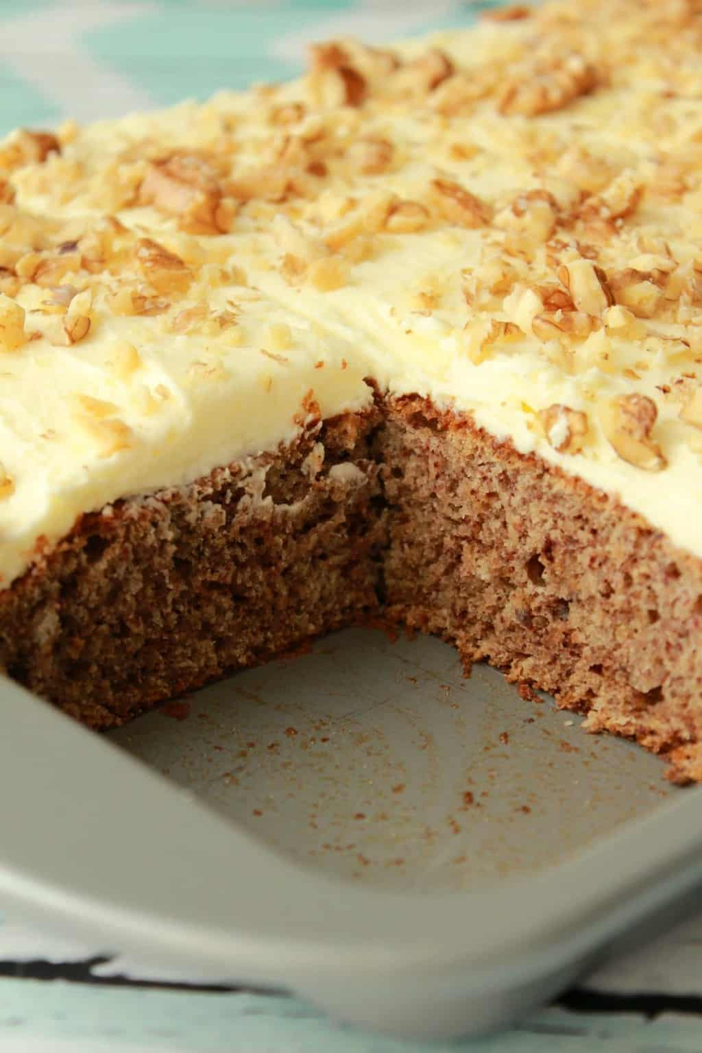 Vegan banana cake topped with lemon frosting and crushed walnuts in a quarter sheet pan with one slice removed.