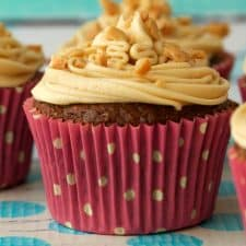 Vegan banana cupcakes topped with frosting and crushed peanuts.