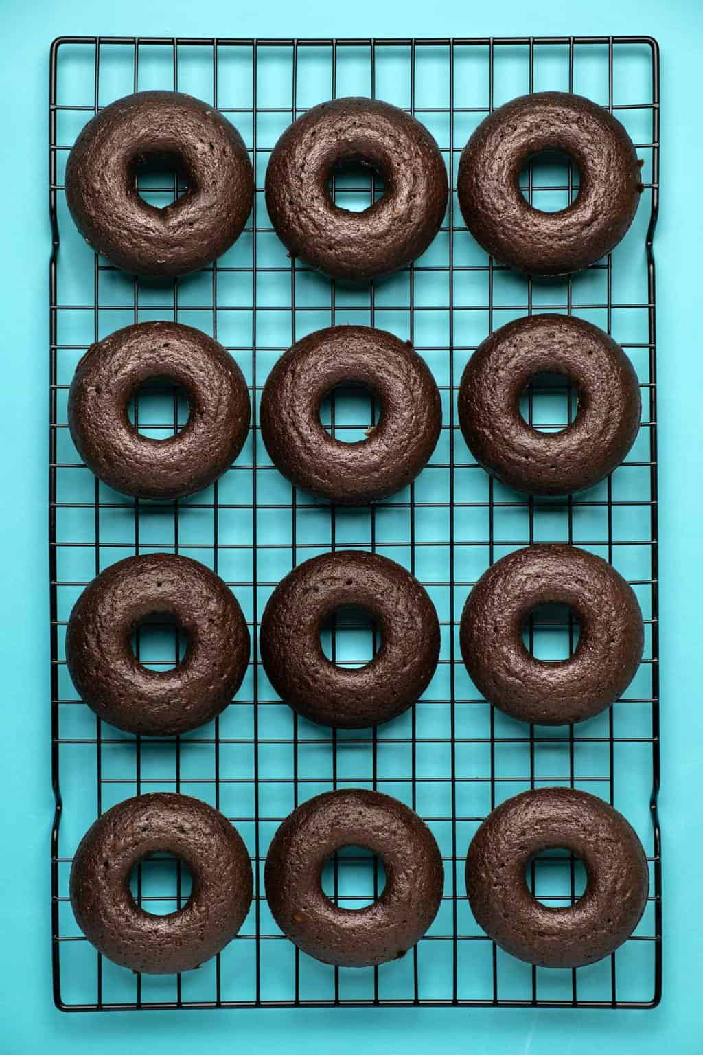 Vegan chocolate donuts on a wire cooling rack.