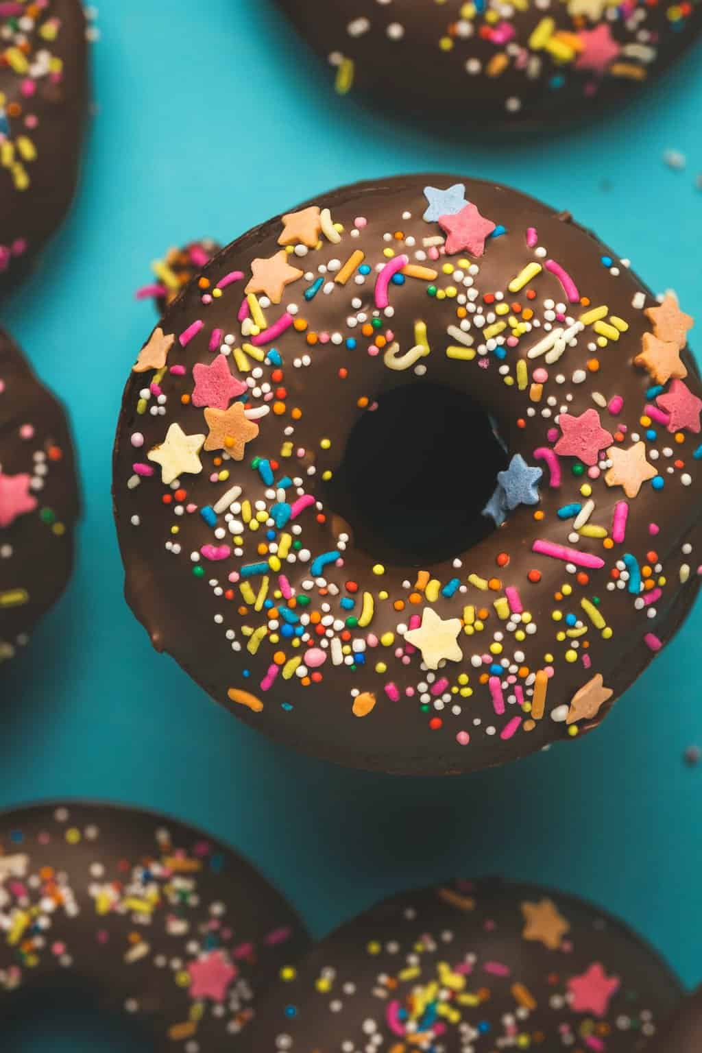 Vegan chocolate donuts topped with sprinkles.