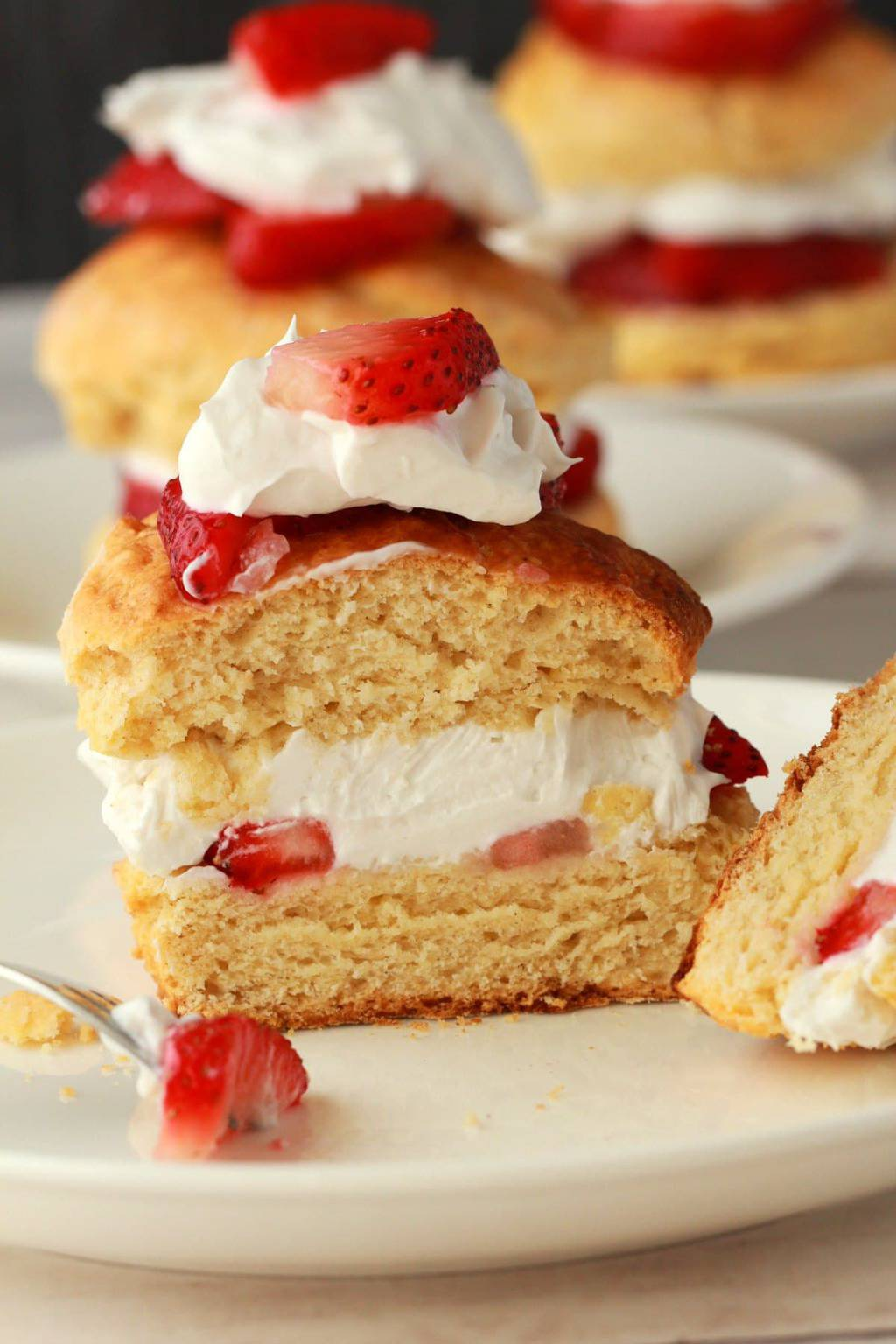 Vegan strawberry shortcake with vegan whipped cream and fresh strawberries sliced in half.