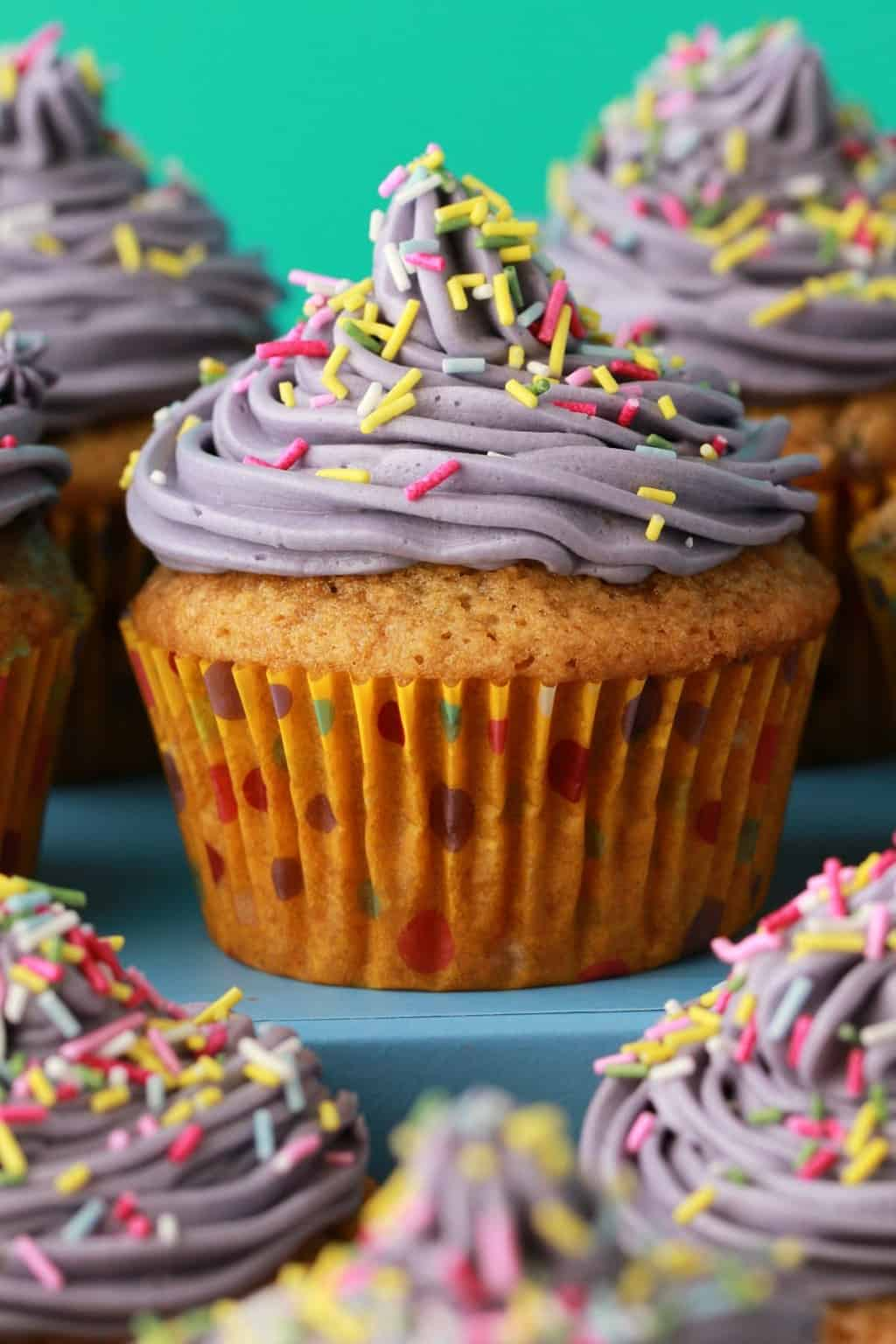 Gorgeously colorful vegan funfetti cupcakes. Moist, light and fluffy vegan cupcakes with purple frosting and plenty of sprinkles! #vegan #lovingitvegan #cupcakes #dessert #funfetti