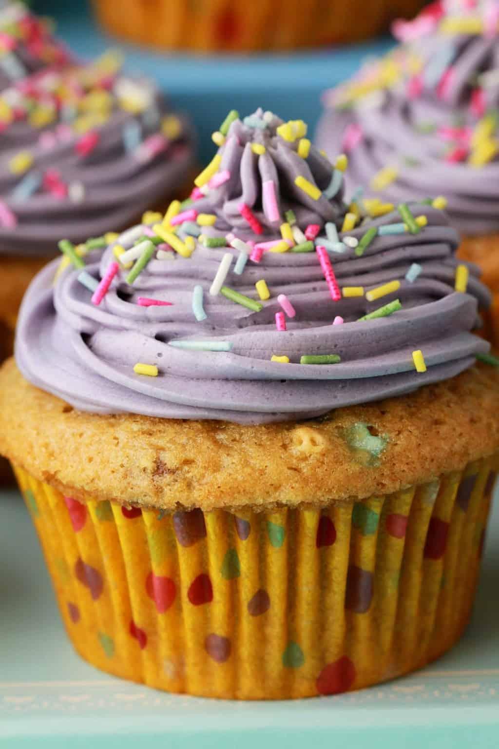 Gorgeously colorful vegan funfetti cupcakes. Moist, light and fluffy vegan cupcakes with purple frosting and plenty of sprinkles! #vegan #lovingitvegan #cupcakes #dessert