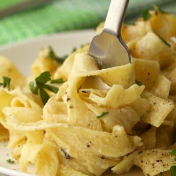 Vegan fettucine alfredo on a white plate with a fork.