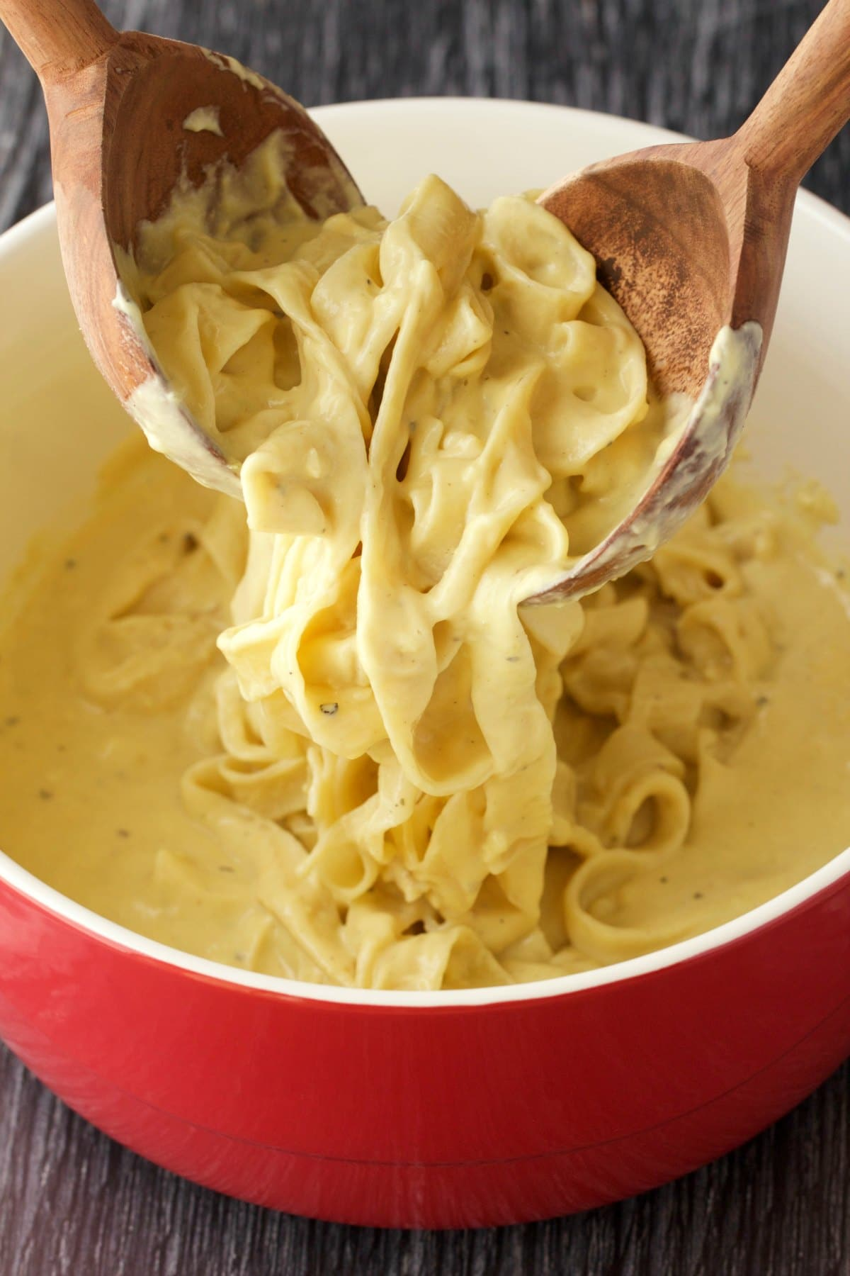 Vegan alfredo with fettucine in a red dish with two wooden serving spoons.