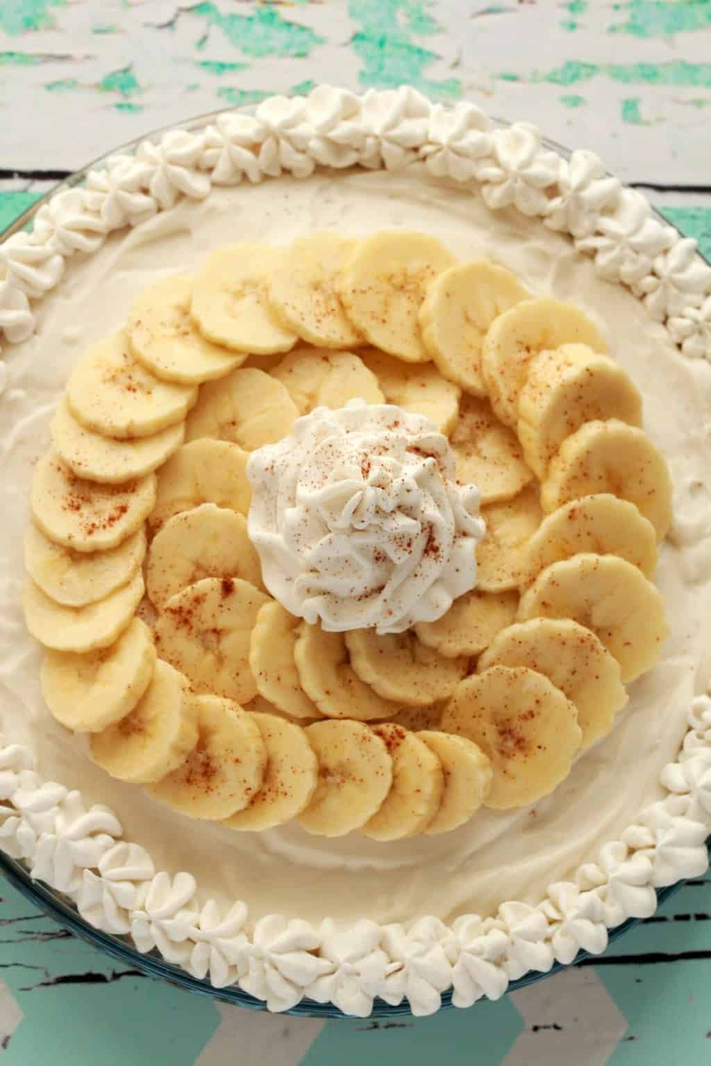 Vegan banana cream pie topped with sliced banana and vegan whipped cream in a glass pie dish.