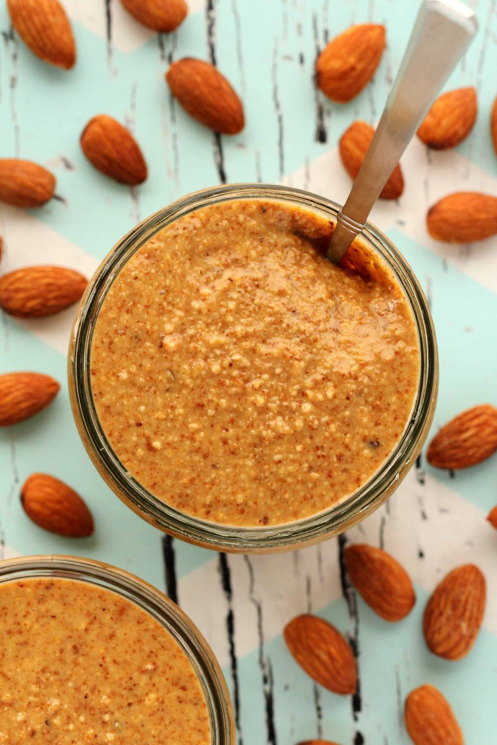 Almond butter in a glass jar with a spoon.