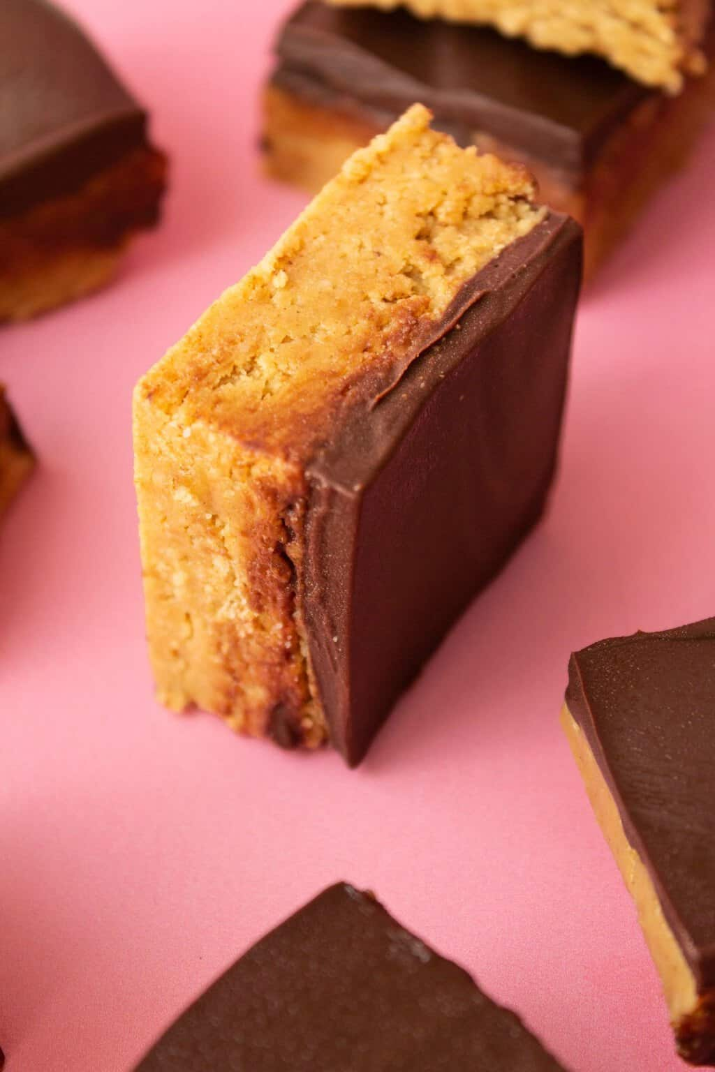 A vegan peanut butter square on a pink surface.