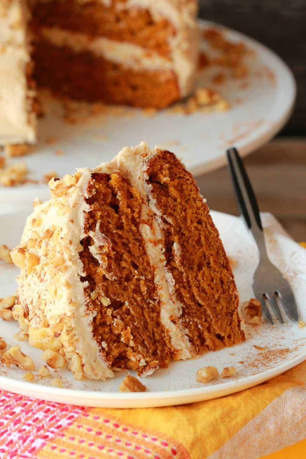 A slice of vegan pumpkin cake on a white plate with a cake fork.