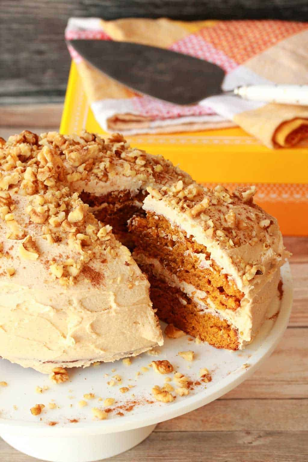 Vegan pumpkin cake topped with cinnamon buttercream and crushed walnuts on a white cake stand.