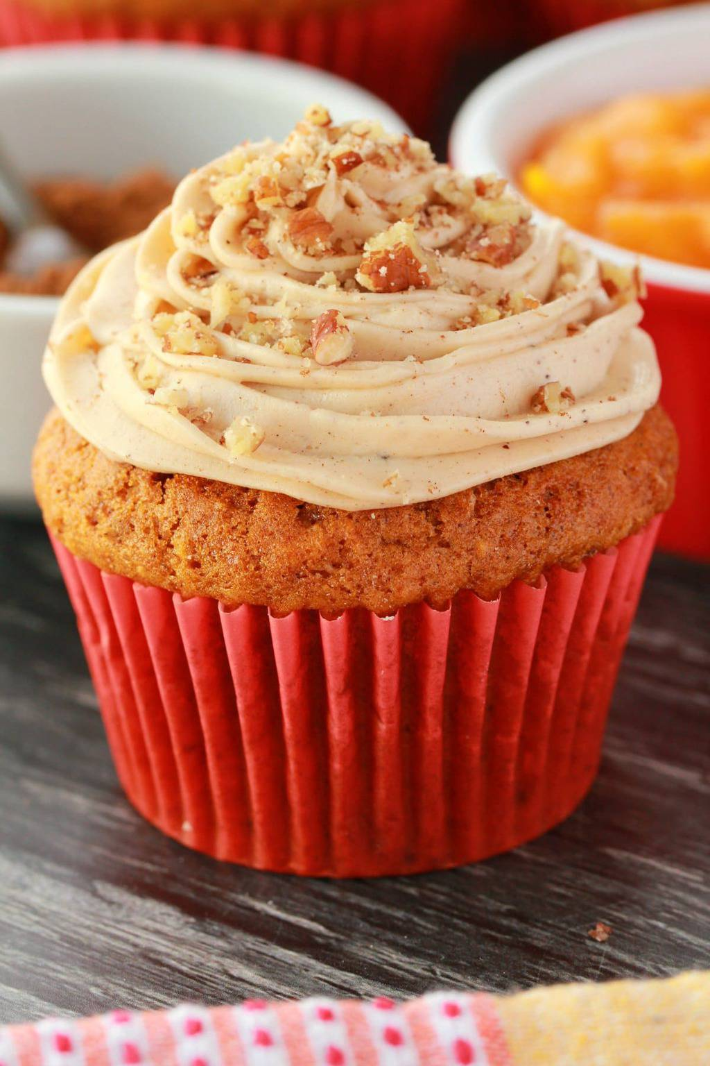 Vegan pumpkin cupcake topped with pumpkin spice frosting and crushed pecans.