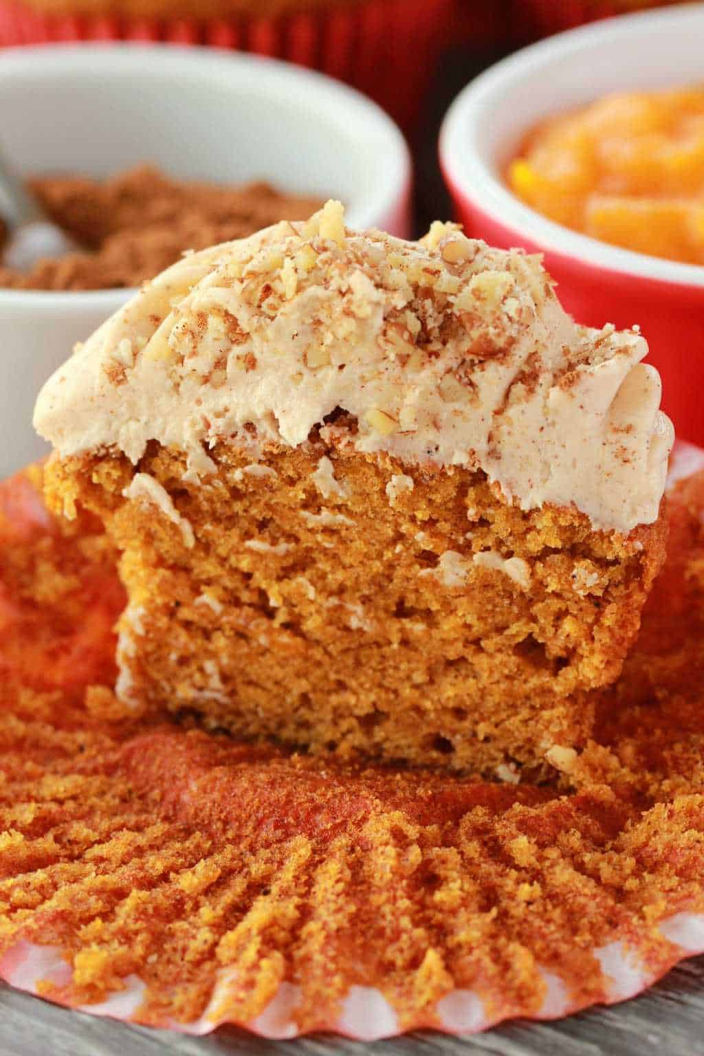 Vegan pumpkin cupcake topped with pumpkin spice frosting, cut in half to show the center.