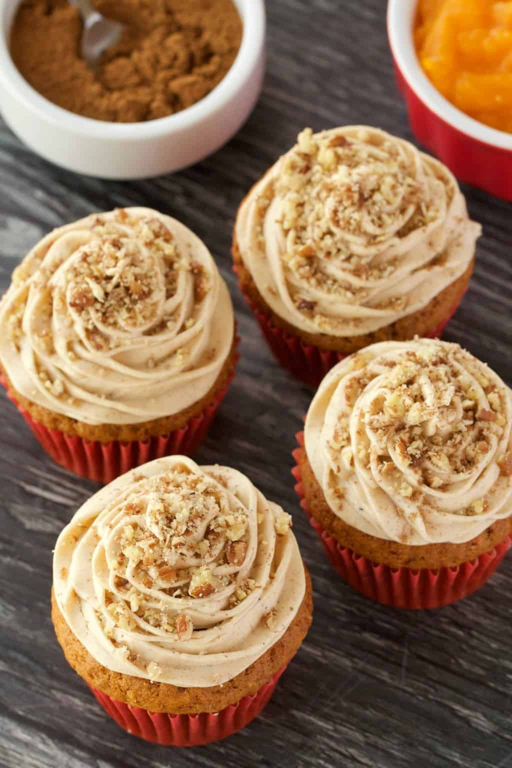 Vegan pumpkin cupcakes topped with a pumpkin spice frosting and crushed pecans.