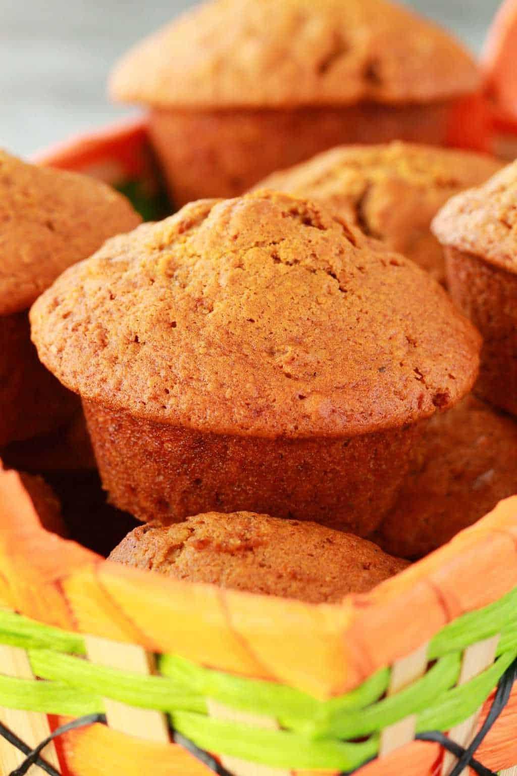 Vegan pumpkin muffins in an orange and green muffin basket.