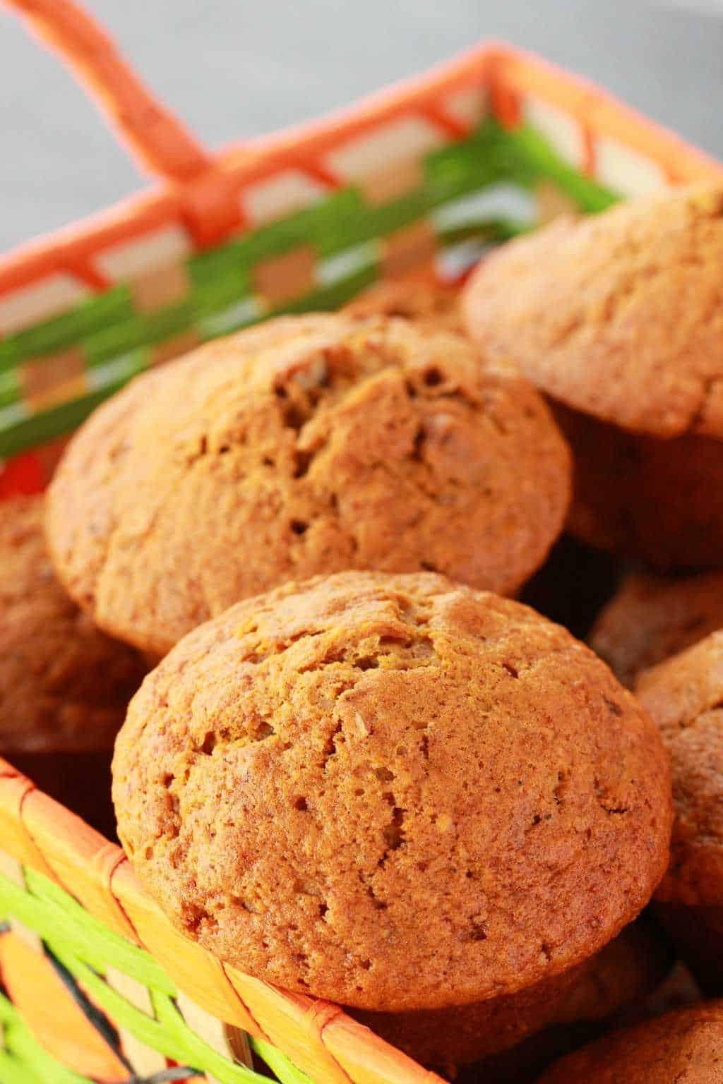 Vegan pumpkin muffins in an orange and green woven basket.