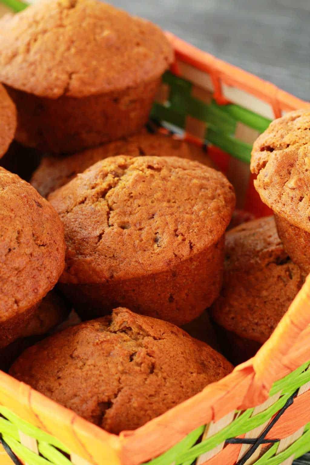 Vegan pumpkin muffins in a green and orange woven basket.