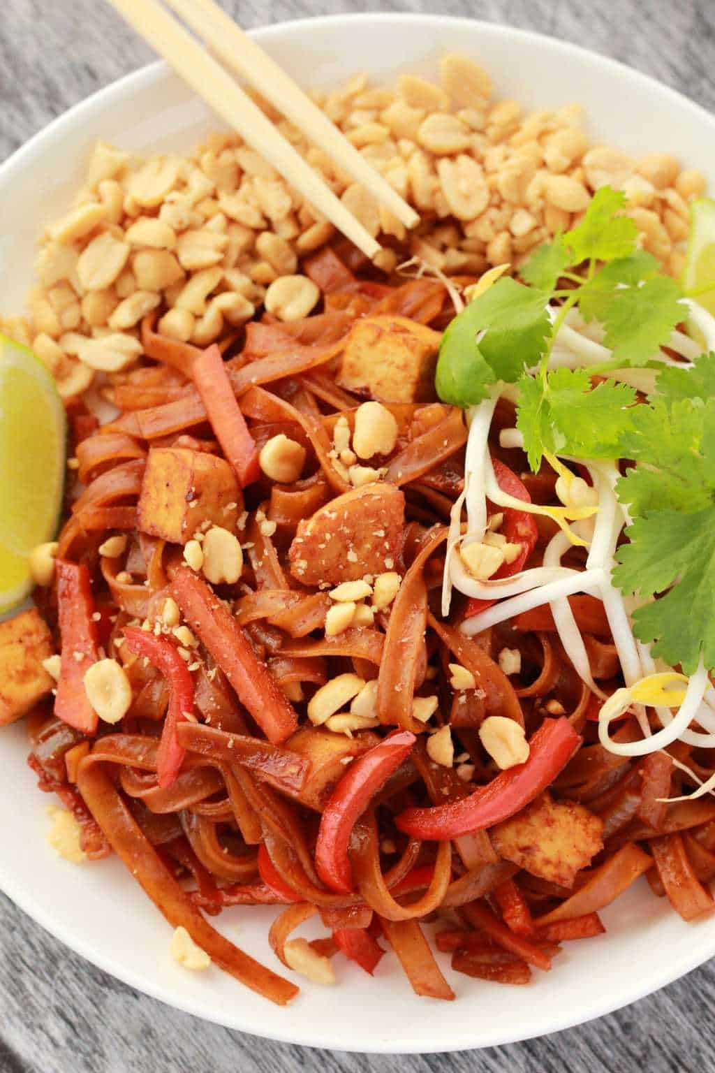 Vegan pad thai topped with crushed peanuts, fresh cilantro and bean sprouts.
