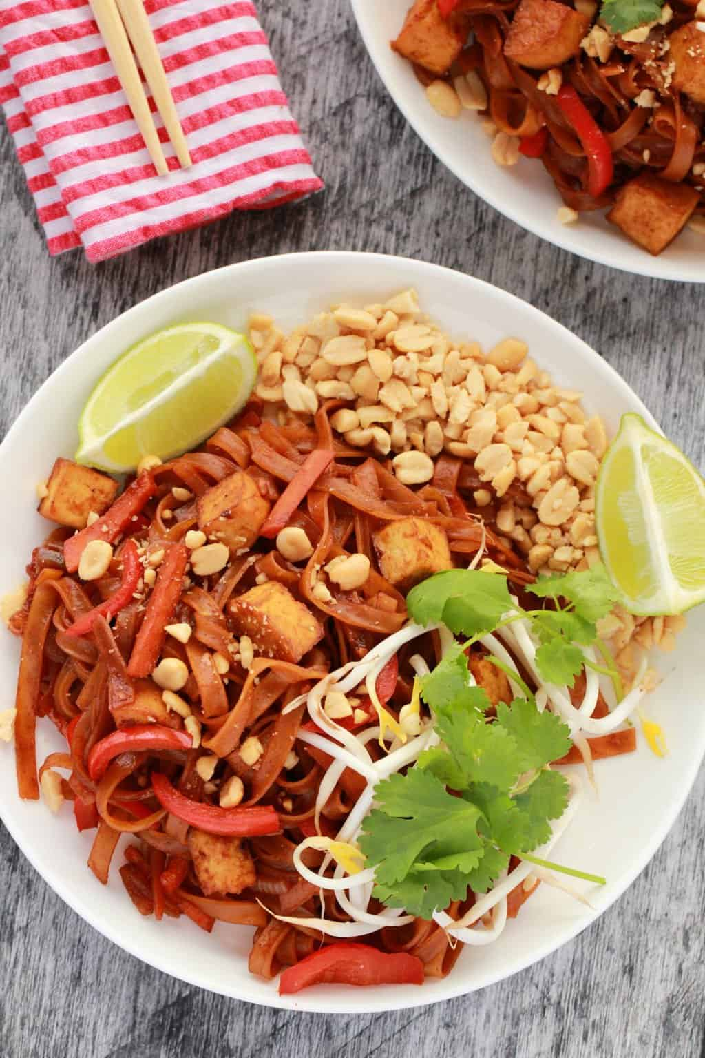 Vegan pad thai topped with fresh cilantro, fresh lime, bean sprouts and crushed peanuts.