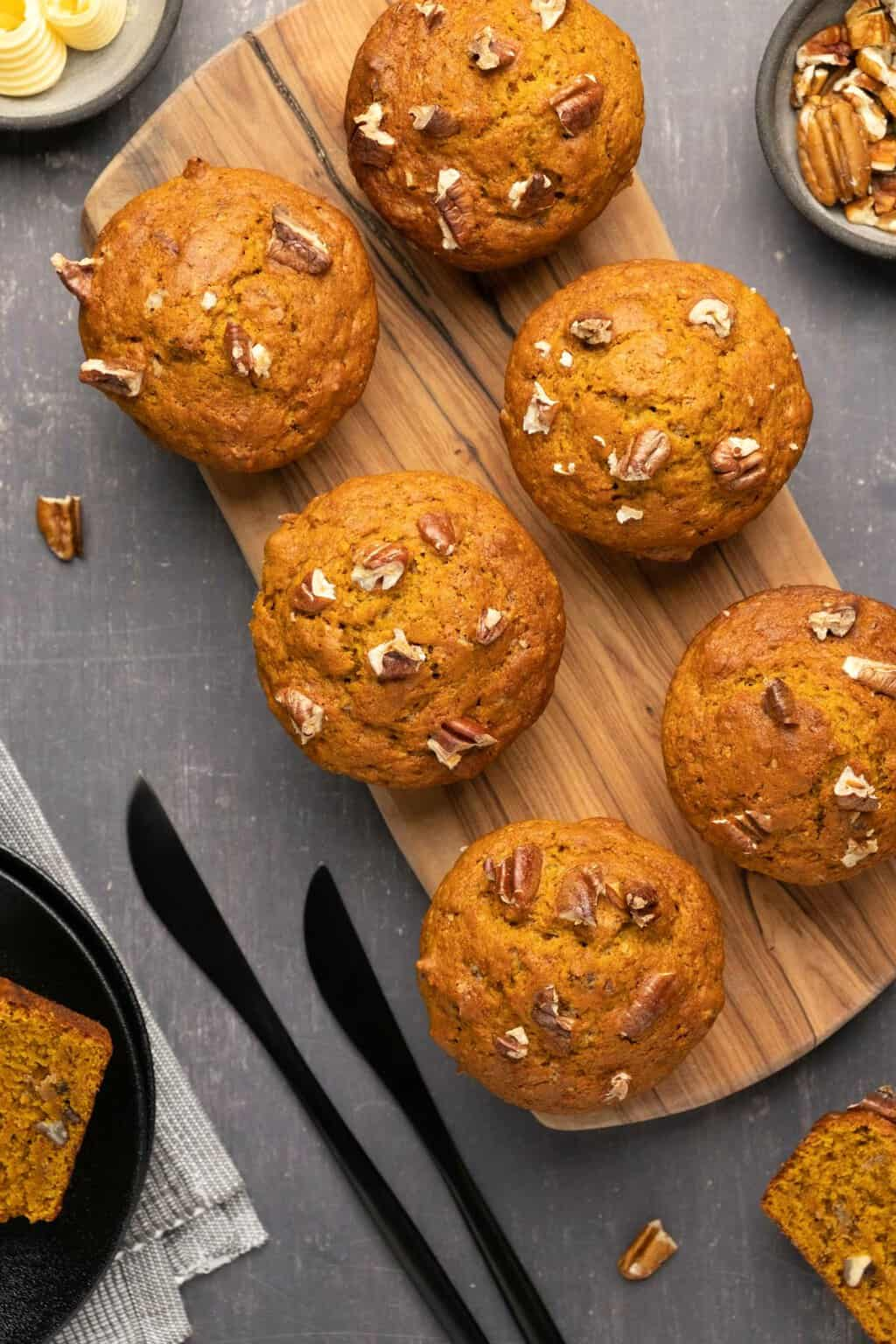 Vegan pumpkin muffins topped with chopped pecans on a wooden board.